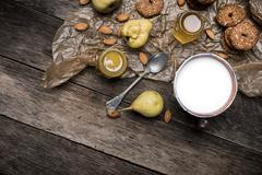 Nuts pears Cookies and milk on wooden table - stock photo