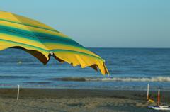 Green and yellow beach umbrella on the sunny beach in summer Stock Photos