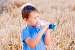 Stock Photo of Boy using inhaler for asthma in village with summer sunset
