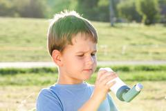 Boy using inhaler for asthma in village with summer sunset Stock Photos