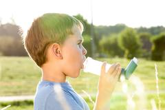 Boy using inhaler for asthma in village with summer sunset - stock photo