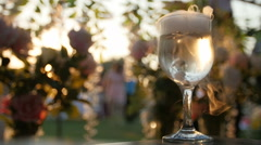 Dry ice on a glass of wine at a reception party in an outdoor sunset scene - stock footage
