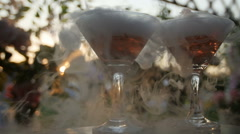 Dry ice on two cocktails at a reception party in an outdoor sunset scene Stock Footage
