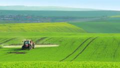 Tractor Sprinkles Plants in the Green Field Stock Footage