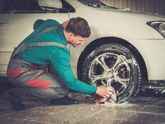 Man worker washing car's alloy rims on a car wash Stock Photos