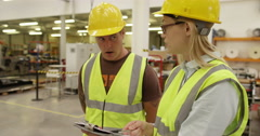 An attractive businesswoman asks some tough questions to her warehouse manager Stock Footage