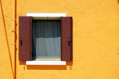 Stock Photo of Brown Window in Burano on orange color wall