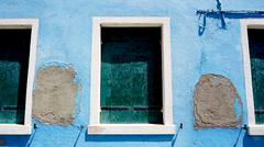Stock Photo of three Windows in Burano on decay blue wall