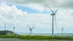Windmill propellers spinning. Green energy generation. Clouds in stormy sky Stock Footage
