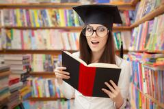 Surprised School Student Reading a Book in a Library - stock photo
