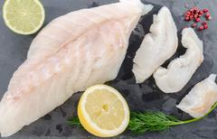 Fresh raw cod fillet on a slate plate - stock photo