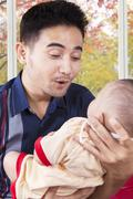 Young dad holding entertain his baby - stock photo