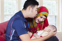 Young parents with newborn baby on sofa - stock photo