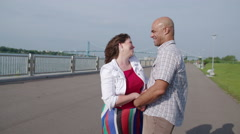 Slow motion couple laugh and walk away from Detroit River 4K - stock footage