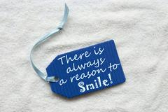 Always Reason To Smile On Blue Label Sand Background - stock photo
