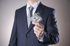 Stock Photo of Businessman with money in studio. Corruption concept