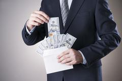 Businessman with money in studio. Corruption concept - stock photo