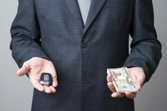 Businessman using car key and money Stock Photos