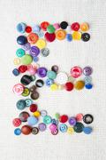 Letter E of the alphabet of buttons of various shapes and colors - stock photo