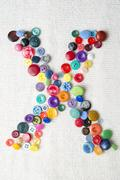 Letter X of the alphabet of buttons of various shapes and colors Stock Photos