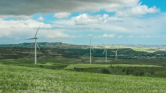 Beautiful green field with wind turbines rotating. Renewable energy source Stock Footage