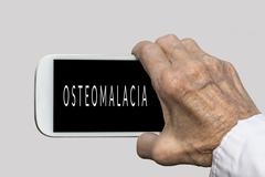 Smart phone in old hand with OSTEOMALACIA text on screen - stock photo