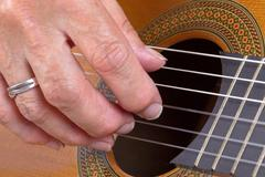 Old woman's hand playing guitar Stock Photos