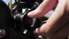Hand puts key into motorbike ignition. Stock Footage