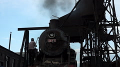 Worker climbing on steam train in servicing factory Stock Footage