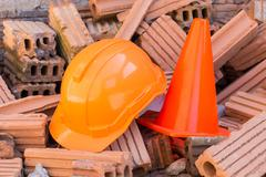 hard hat safety helmet and cone in construction site - stock photo