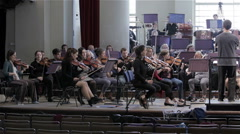 Orchestra rehearsal: slow pan across symphony orchestra Stock Footage