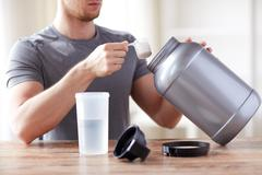 close up of man with protein shake bottle and jar - stock photo