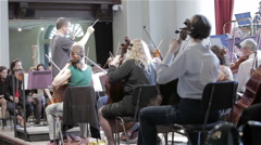Orchestra rehearsal: conductor and string section Stock Footage