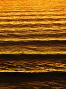 Sea wave ripples at sunset Stock Photos