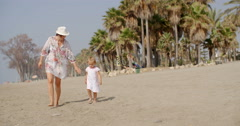 Mother walking on a beach with her small daughter - stock footage