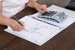 Female Accountant Calculating Bills With Calculator In Office Stock Photos