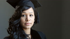 Portrait of a young woman graduate in cap and gown - stock footage