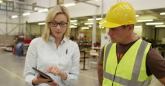 A confident businesswoman talks to a warehouse worker in a warehouse Stock Footage