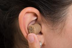 Close-up Of Woman Ear Wearing Hearing Aid - stock photo