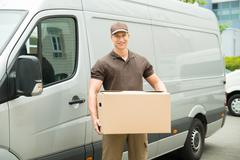 Happy Delivery Man Holding Box In Front Van - stock photo