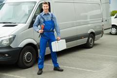 Happy Male Worker With Work Tool And Toolbox In Front Of Van - stock photo