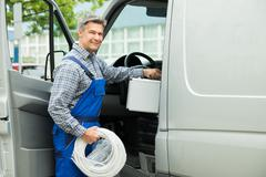 Happy Male Worker With Toolbox And Cable Coil Entering In Van - stock photo
