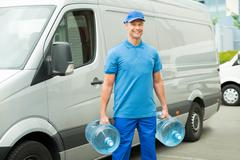 Delivery Man With Two Large Water Bottles Standing In Front Of Delivery Van - stock photo
