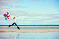 Beautiful girl jumps on the beach while holding colored balloons Stock Photos
