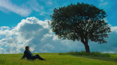 Young woman enjoying solitude under green tree. Relaxation alone with nature Stock Footage