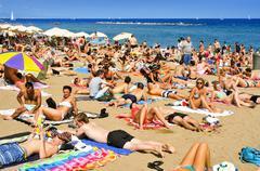 sunbathers at La Barceloneta Beach, in Barcelona, Spain - stock photo
