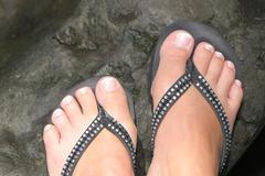 Feet under black background - stock photo