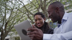 4k Happy attractive ethnic couple using computer tablet outdoors in the city - stock footage