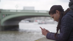 4K Woman on her own in London, using mobile phone by the River Thames Stock Footage