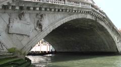 Tourists in gondola under Ponte di Rialto bridge Stock Footage